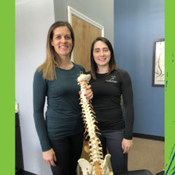 Two female students holding skeleton anatomical model.