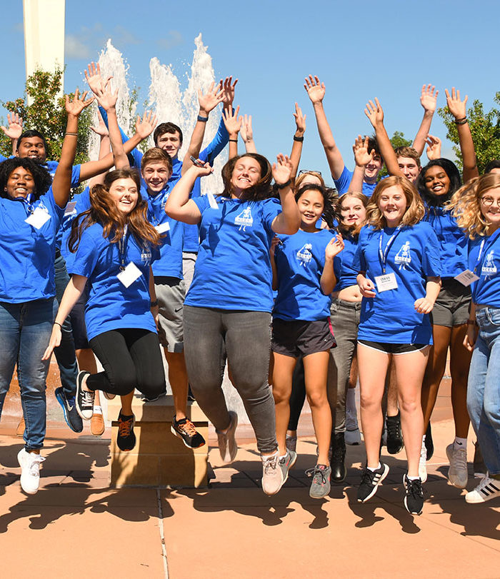 ACES students jumping for a photo outside.