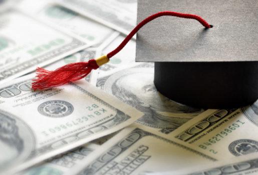 Graduation cap on top of money.