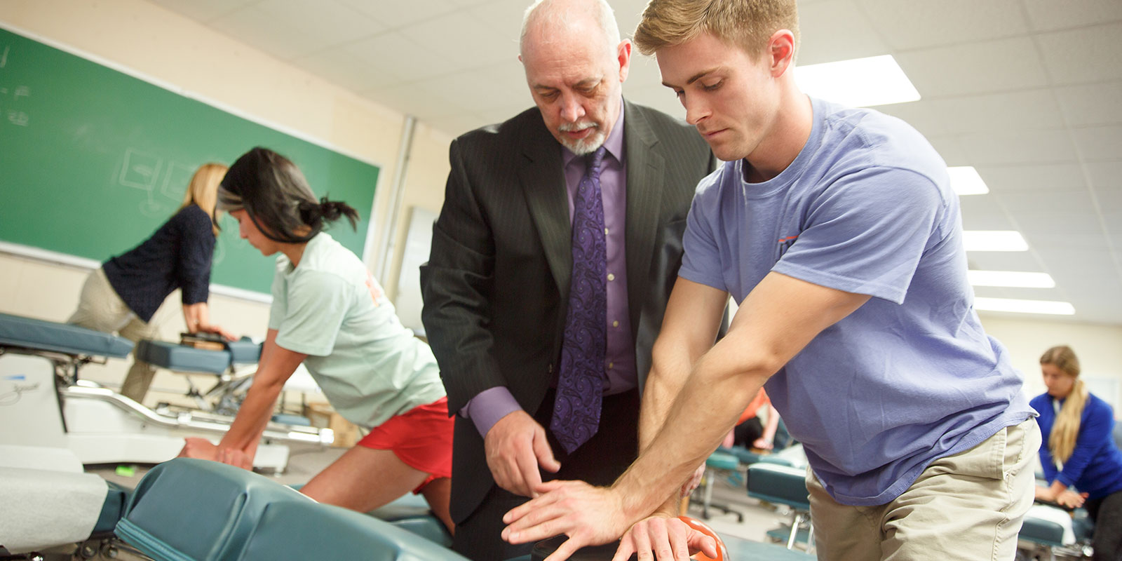 Student working with teacher on chiropractic technique.