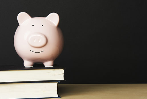 Piggy bank on top of books.