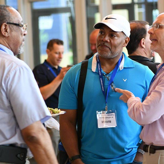 Three men talking at the Purser Center.