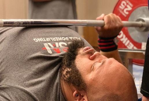 Para-powerlifter bench pressing weights.