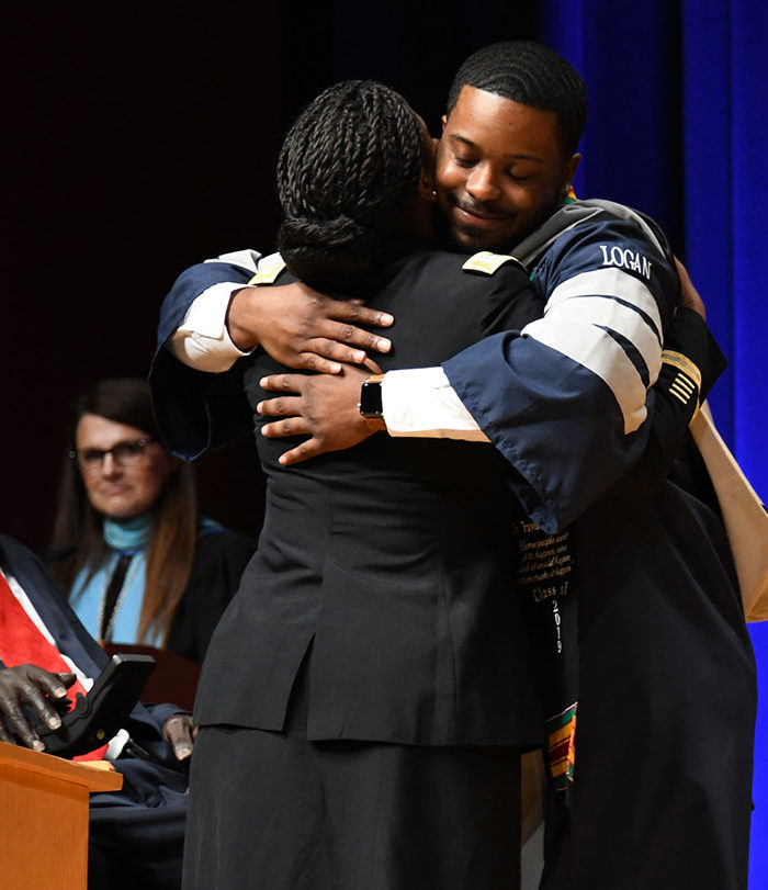 Male student hugging teacher at graduation.