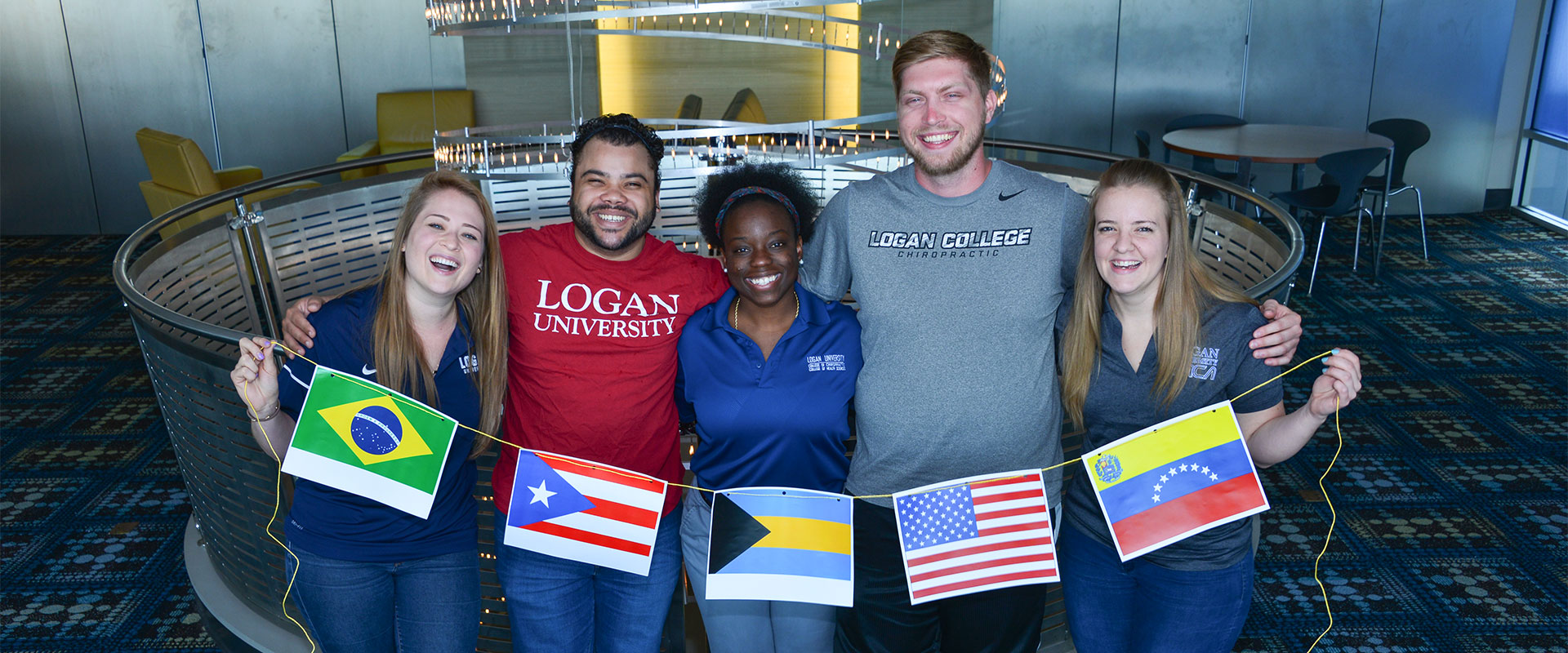 Group of international students smiling and holding flags.