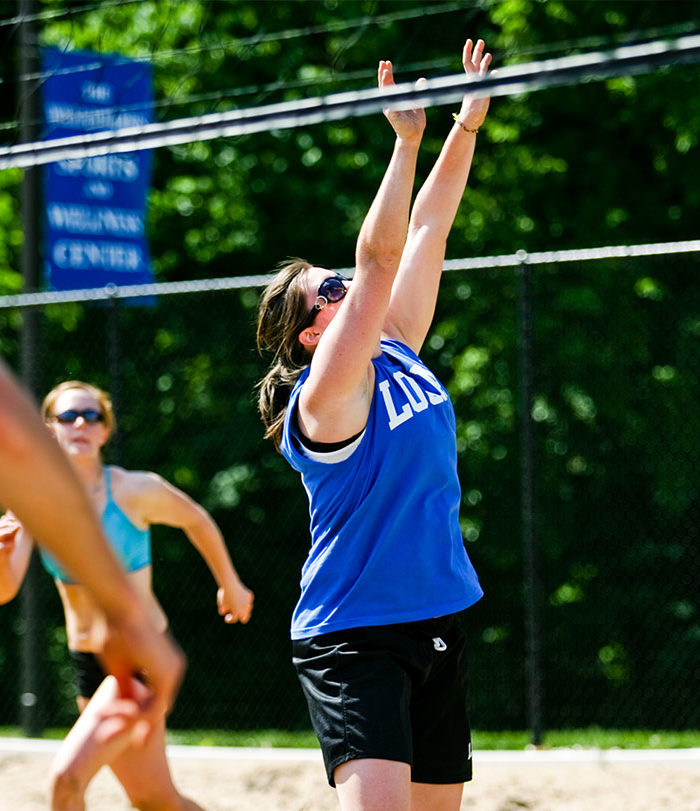 Female student playing sand volleyball on campus.