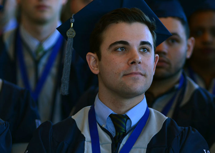 Male student sitting during graduation.