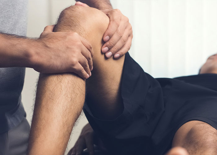 Doctor helping patient rehab knee.