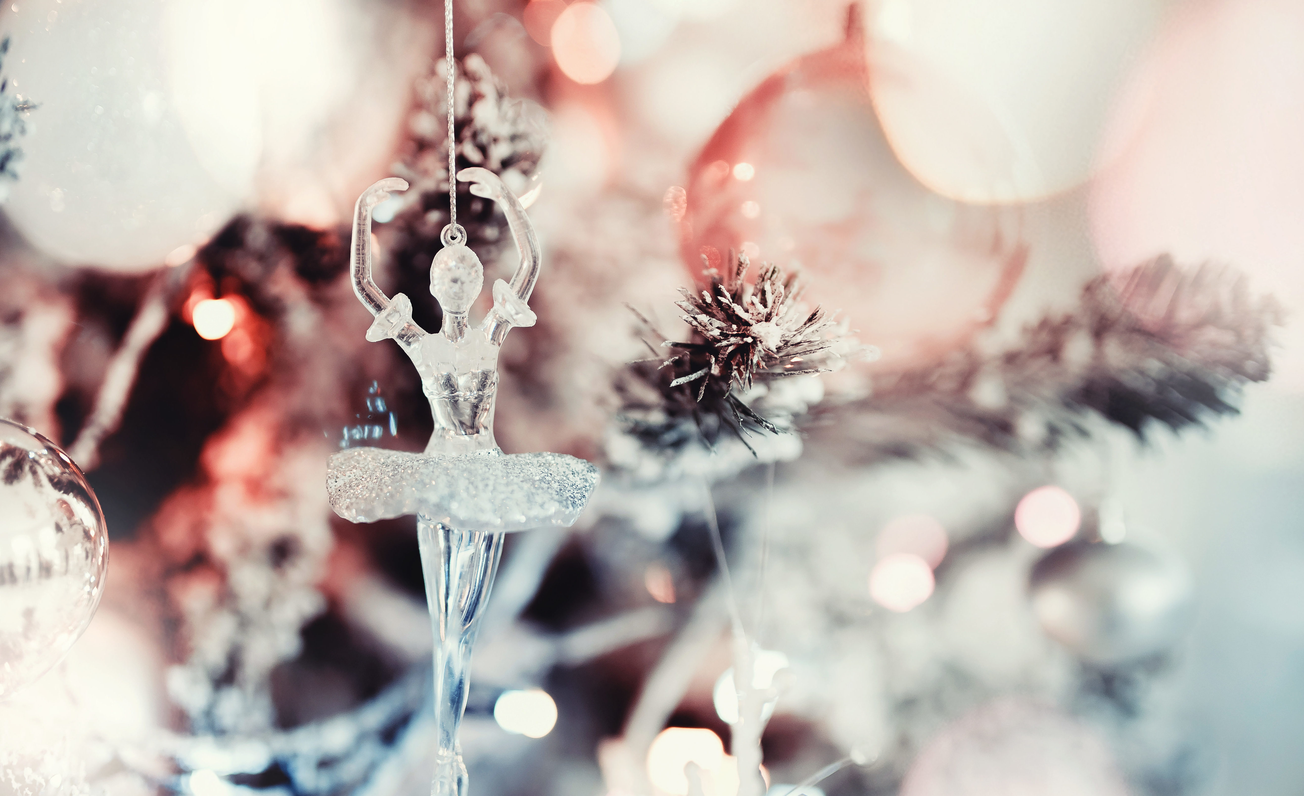 Glass ballerina ornament hanging on snow-dusted Christmas tree