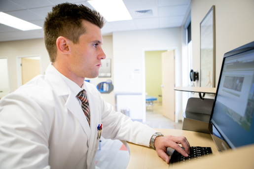 A male health center clinician consults with a patient via telehealth on a desktop computer