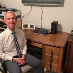 Dr. Filson sits at his desk, which belonged to Dr. Logan