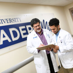 A male doctor of chiropractic and chiropractic student in white coats look at a clipboard and discuss how to become a chiropractor