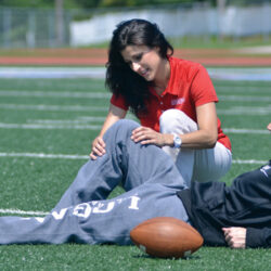 An athletic trainer works on a football player's knee as he lies down on a green turf football field