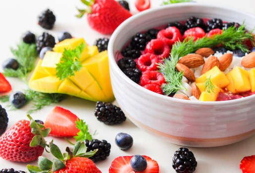 A bowl of fruit, nuts and vegetables sits on a table