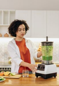 A woman makes a green smoothie in a blender as part of a nutrition masters program