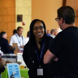 A woman and a man enjoy a conversation at Logan University Symposium