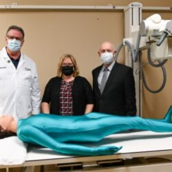 Three people stand behind a full-body radiology phantom lying on a table.